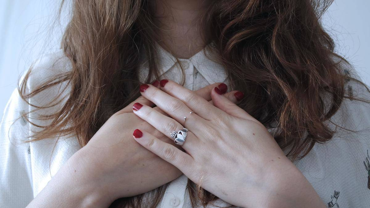 woman puts her hands on her chest in self love