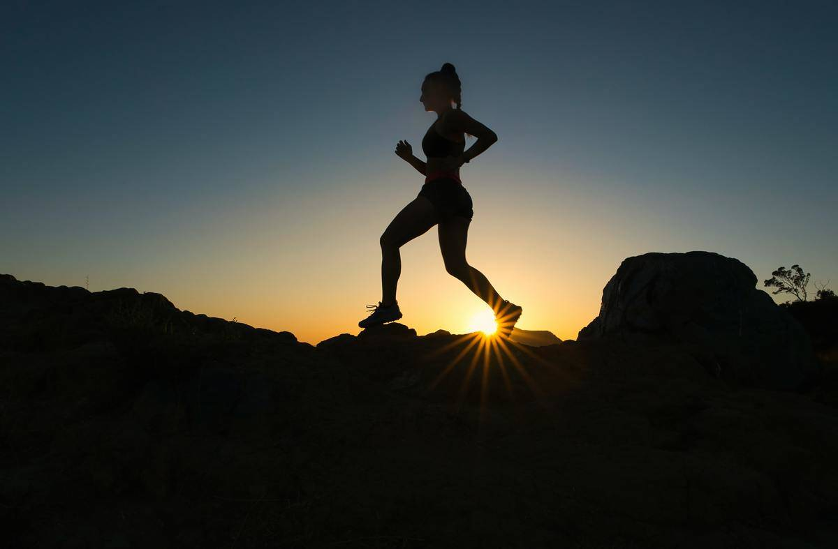 woman running on a cliff with the sunrise