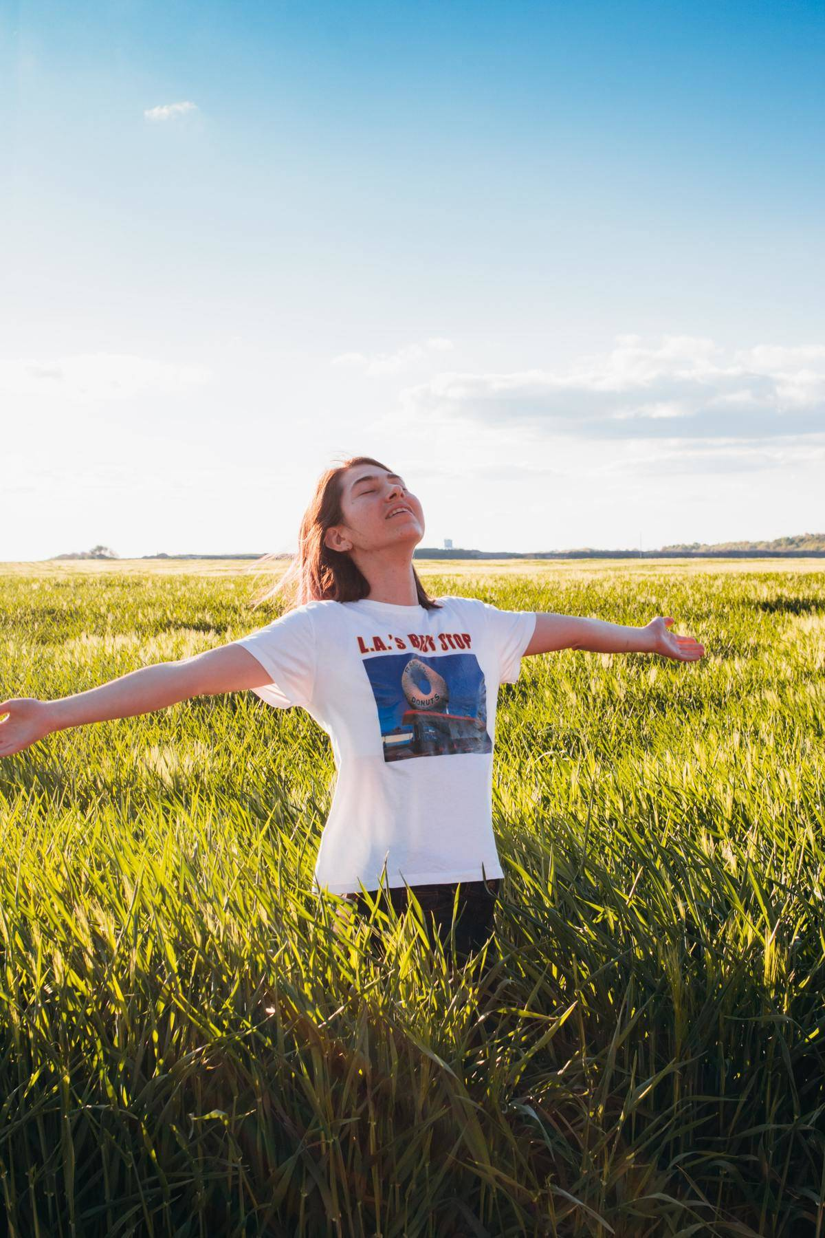 woman stands in field with arms open