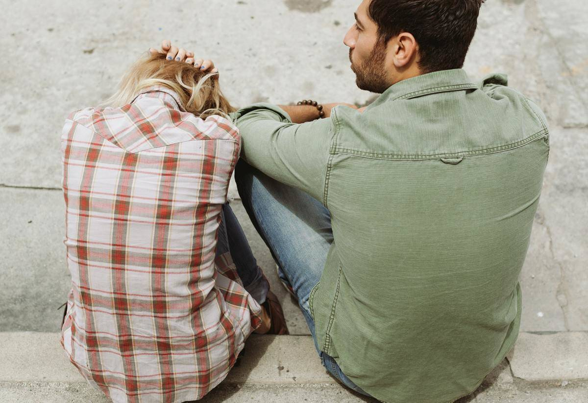 woman in plaid seated on curb with man in green
