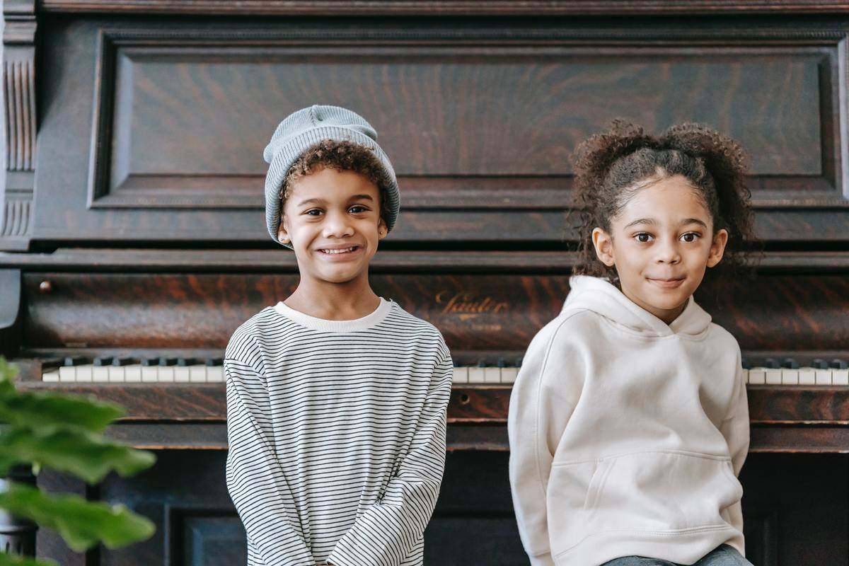 young brother and sister in front of piano