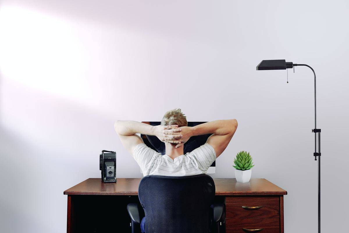Man sits alone at computer with fingers interlocked behind head, thinking