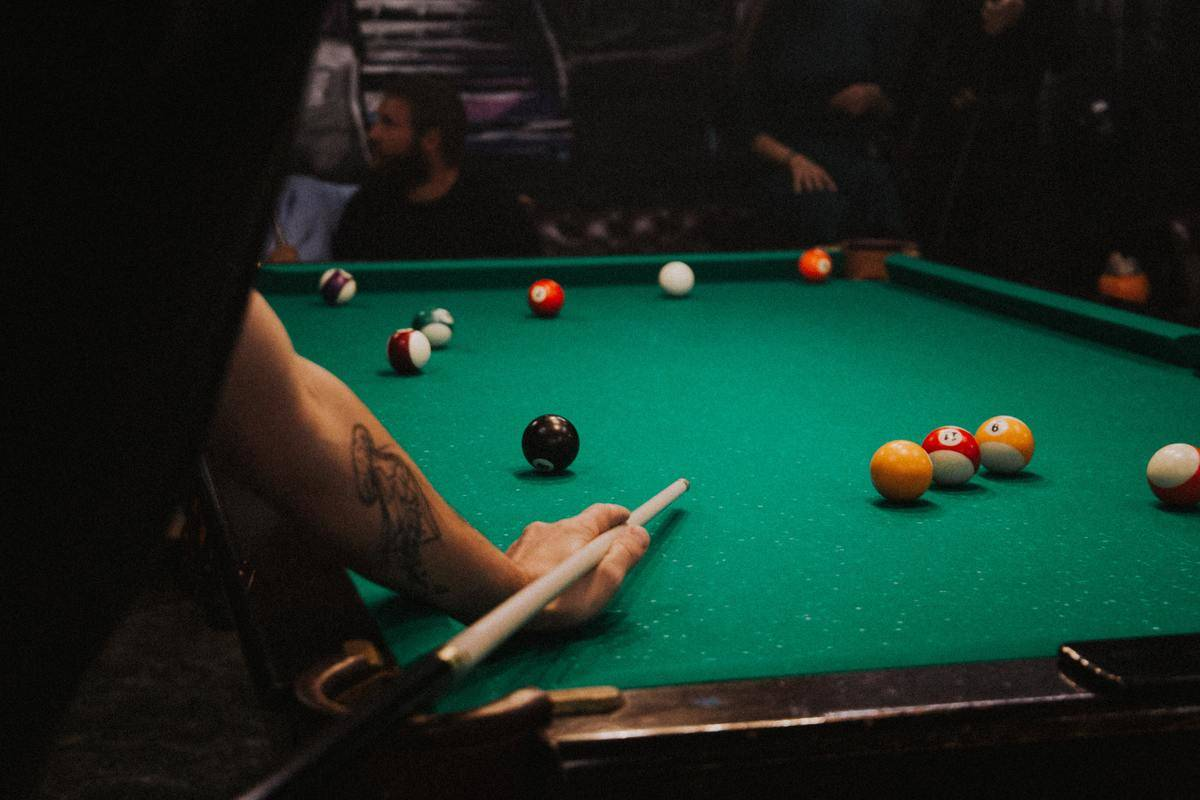 Man playing pool with cue in hand at bar