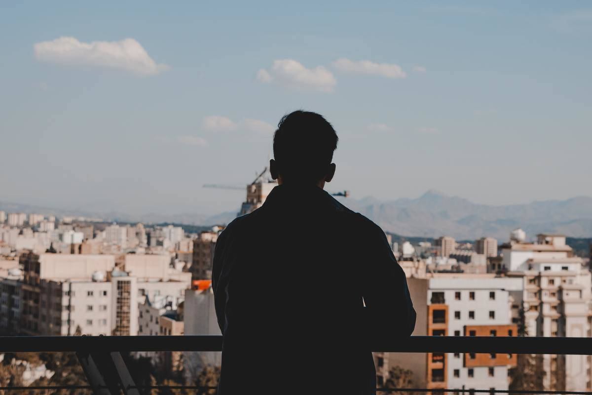Man stands alone overlooking on balcony overlooking city skyline