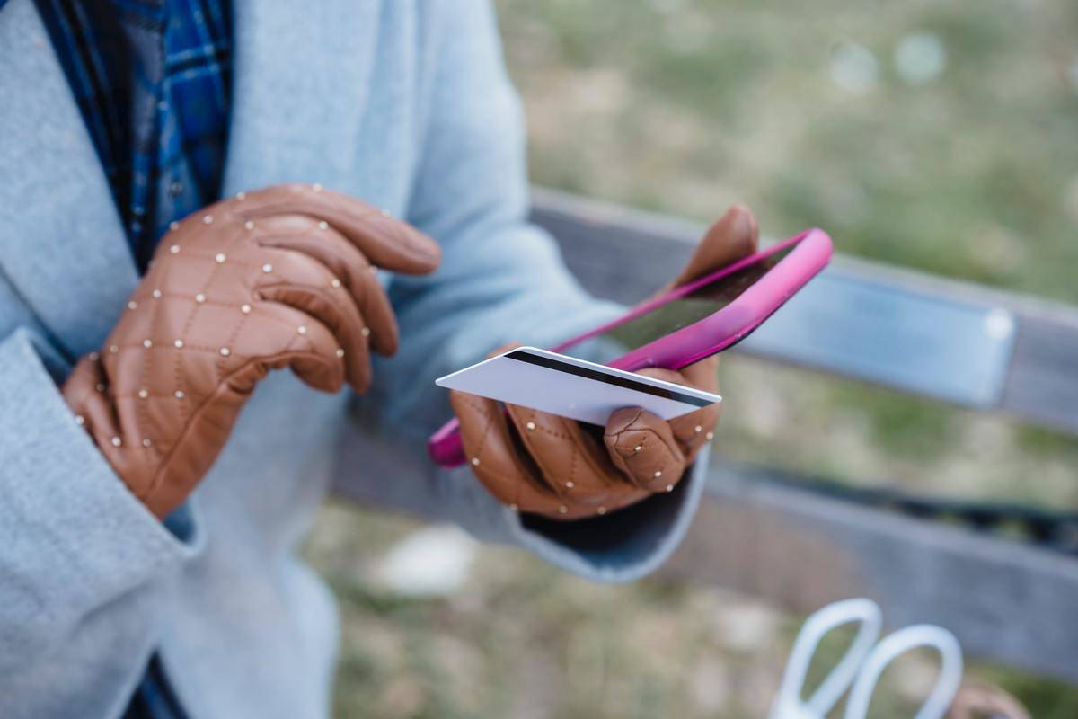 Woman wearing brown leather gloves holding phone in pink phone case, also holding credit card
