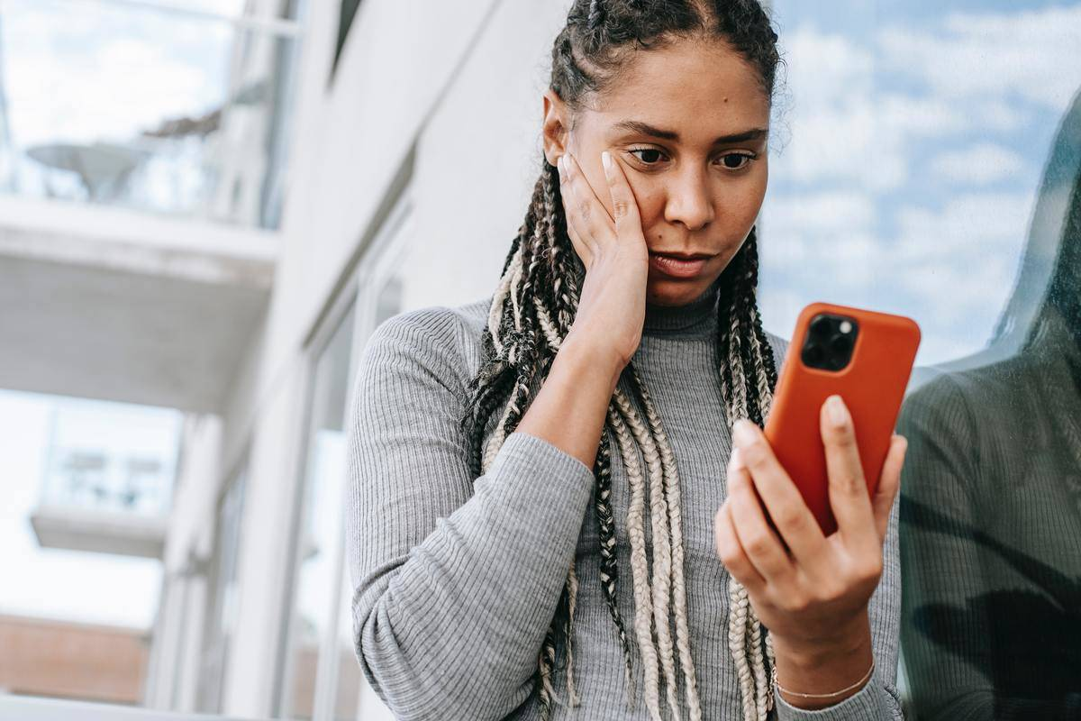 Woman stares at phone with hand pressed to face