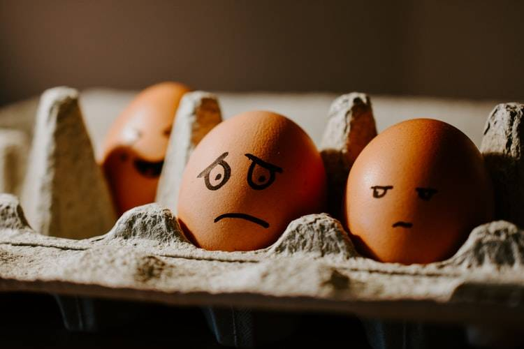 carton of eggs with facial expressions drawn onto them