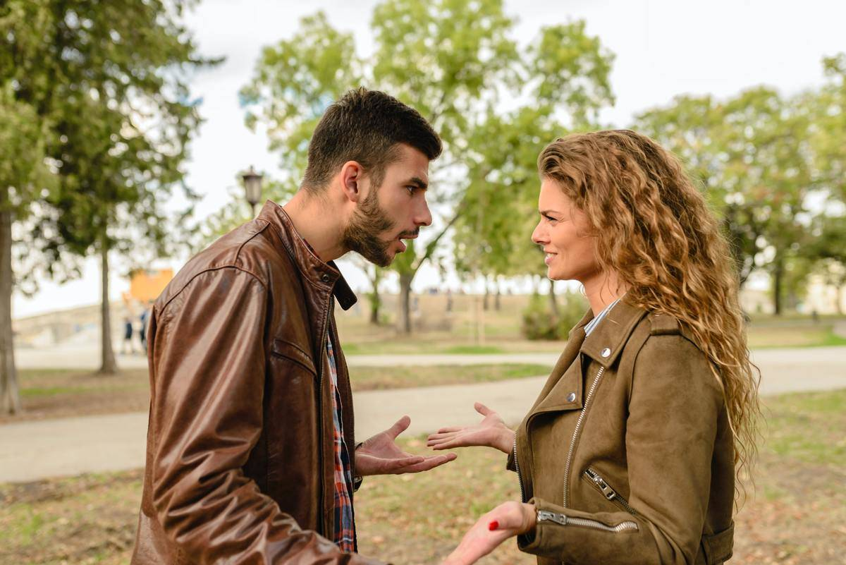 couple in leather jackets fighting in park