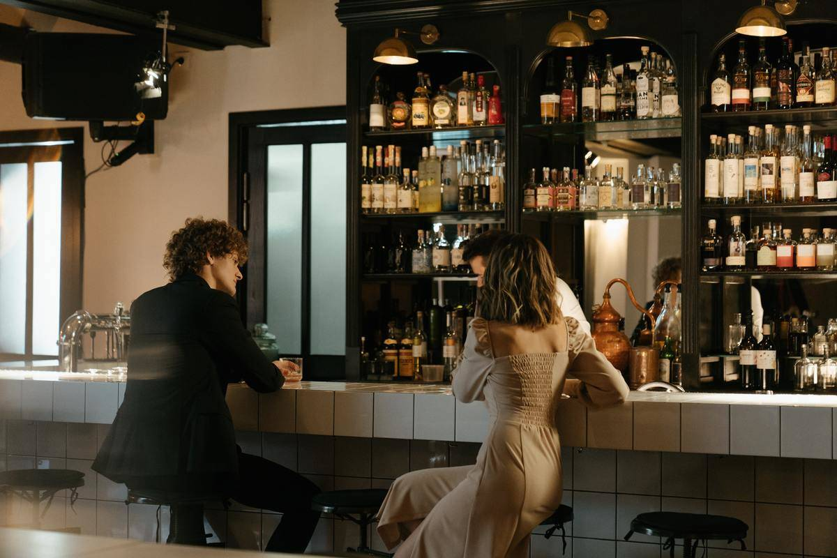 man and woman at bar seated on stools facing each other