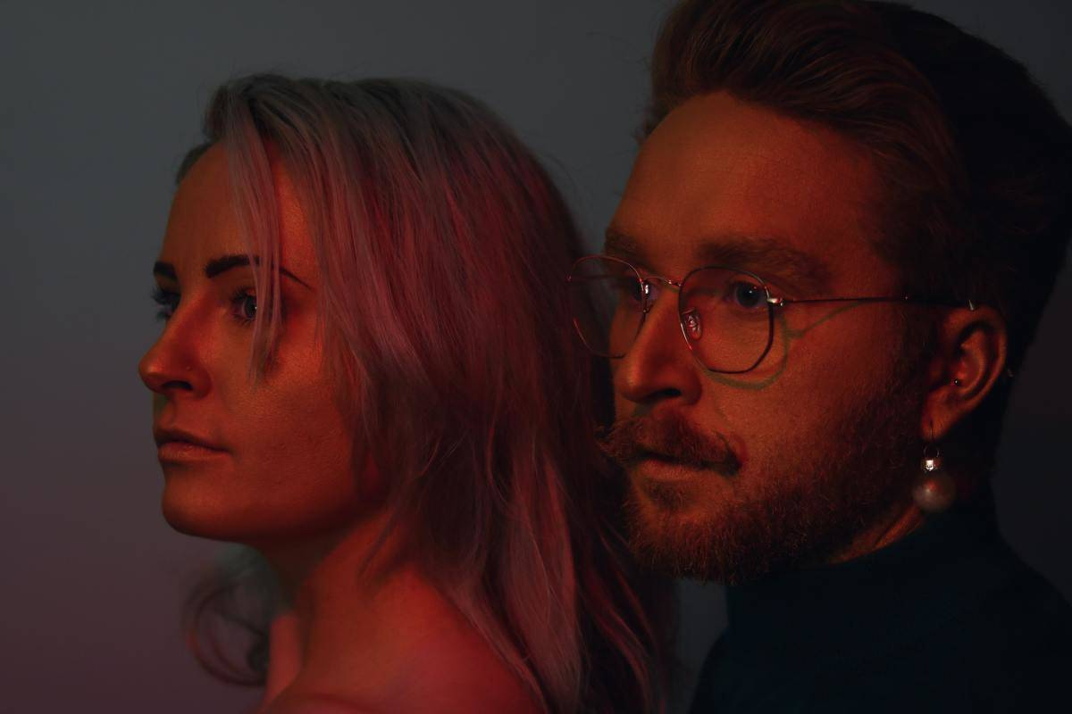 couple in red lighting looking into distance