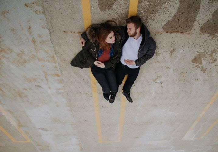 couple lying together on a road