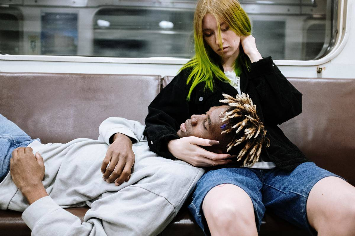 woman on subway with man lying his head in her lap