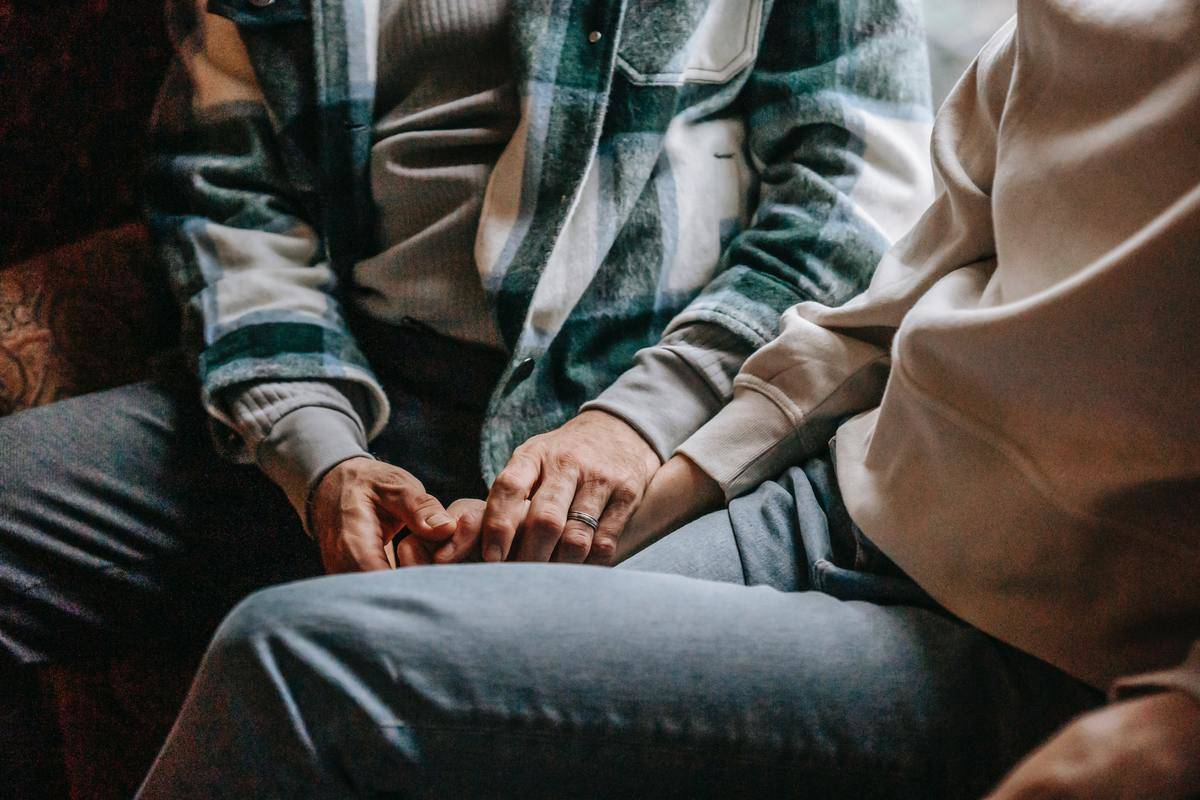 couple in jeans seated holding hands