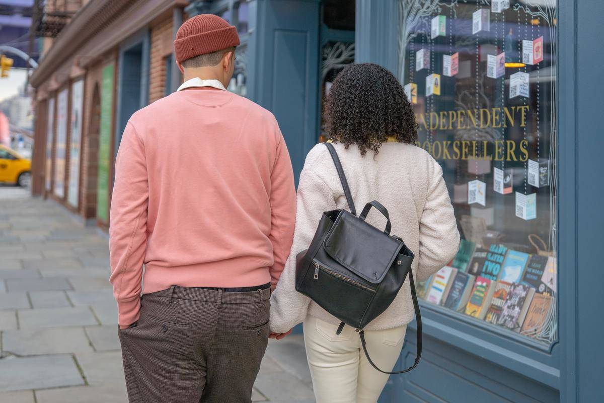 couple walking outdoors past stores