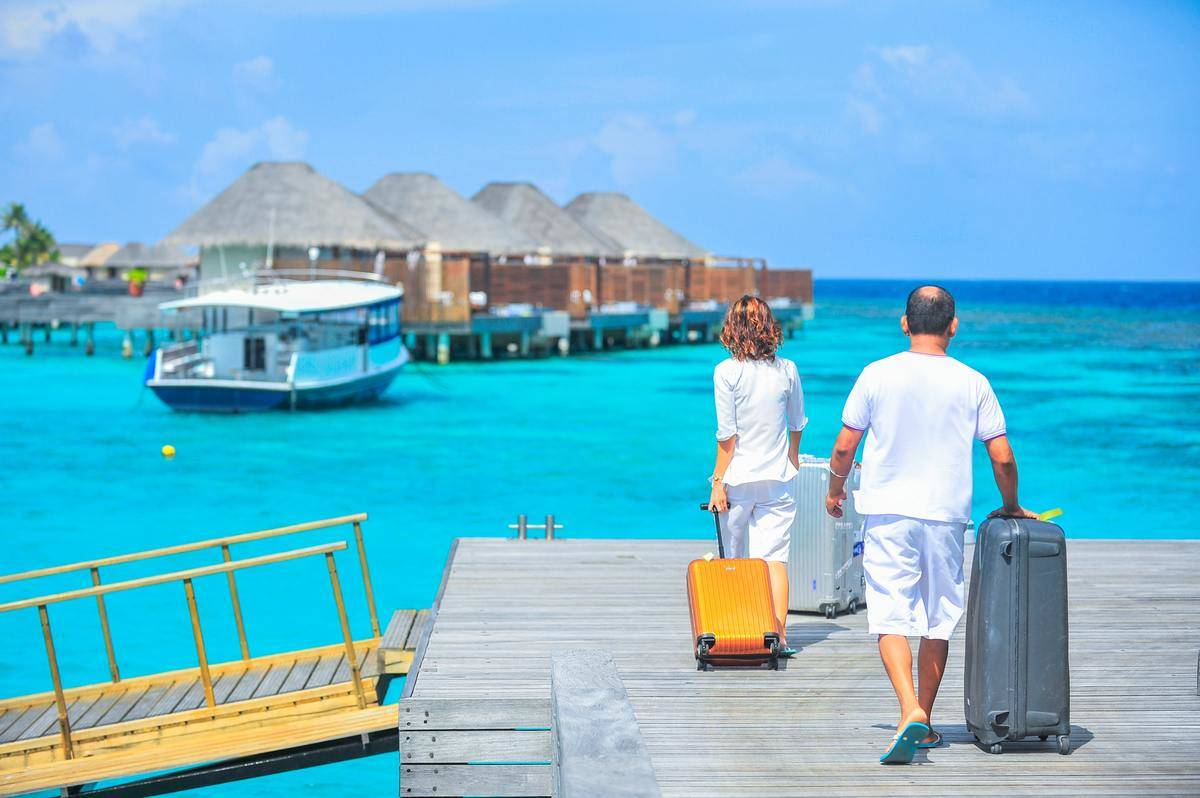 couples in Maldives carrying suitcase