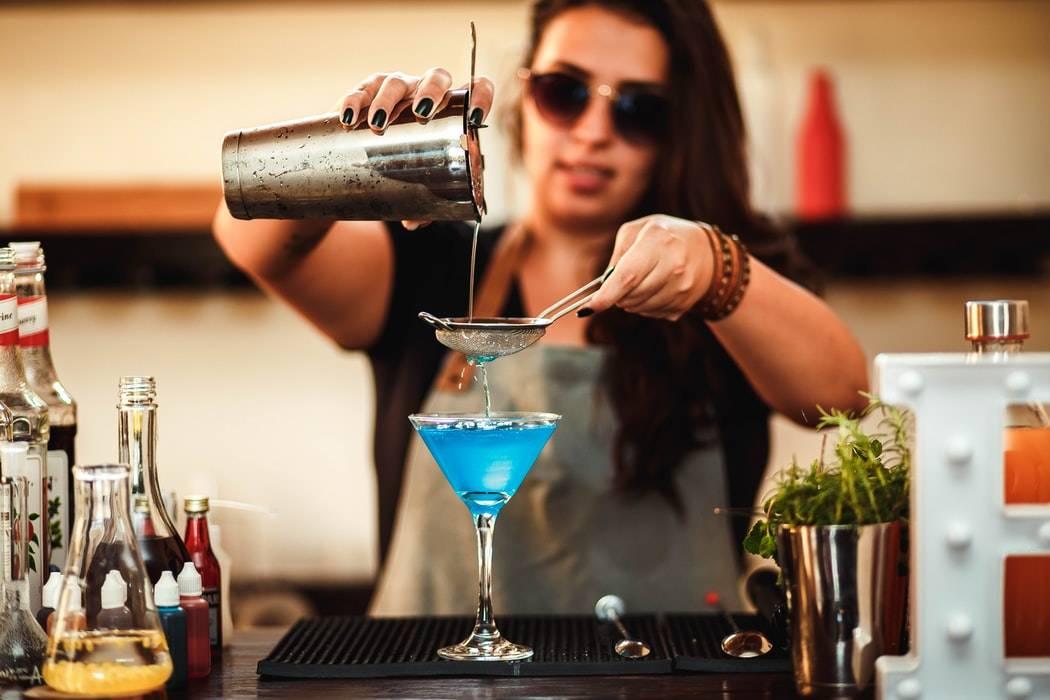 woman pouring blue coloured liquid into martini glass