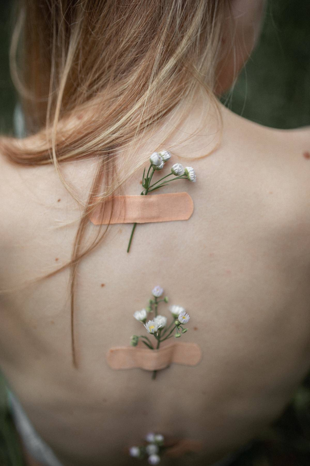 flowers attached with Band-Aids on woman's back