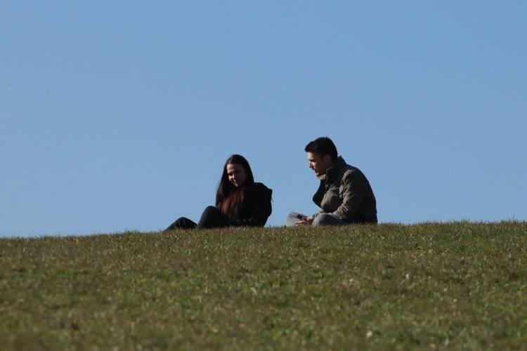 couple sitting on hill and talking to one another