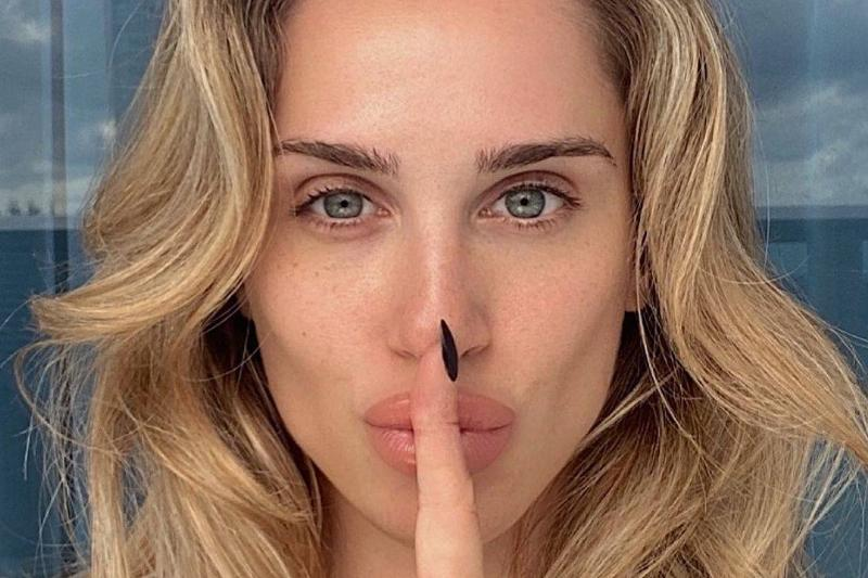 influencer puts one finger in front of her mouth