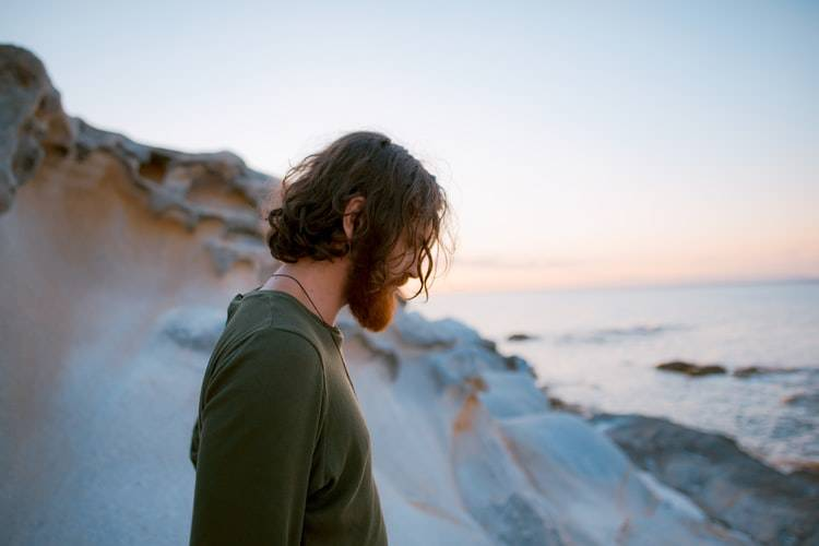 long-haired man by the beach looking down at the ground
