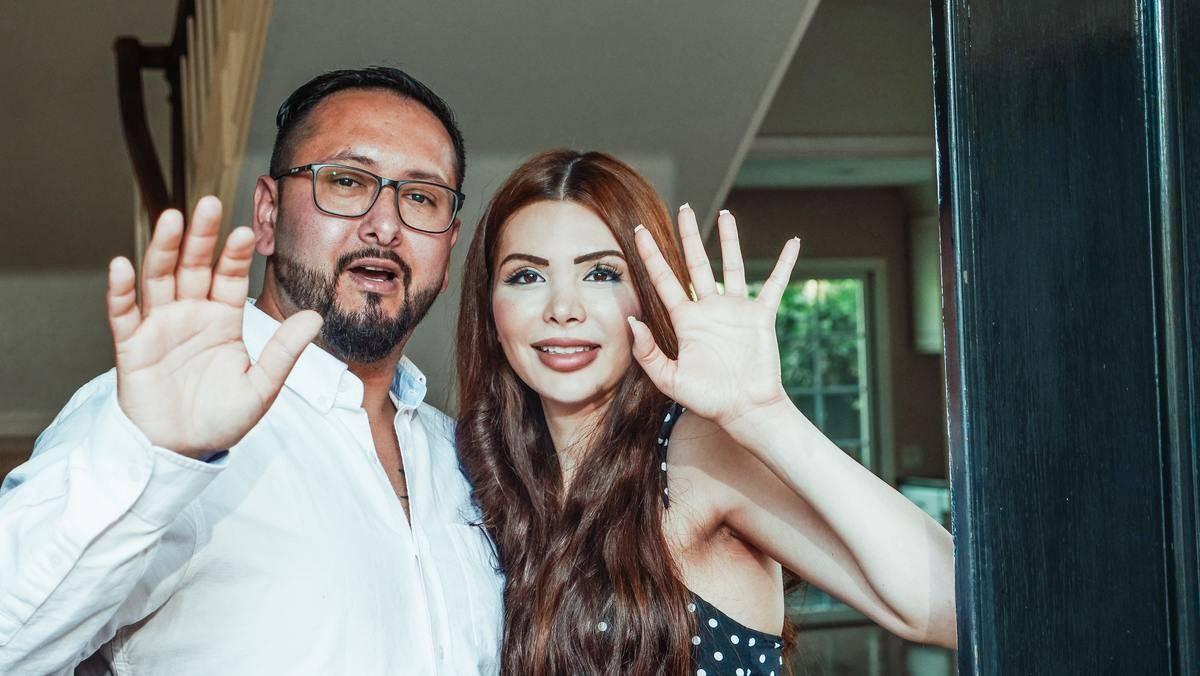 man and woman at the door waving