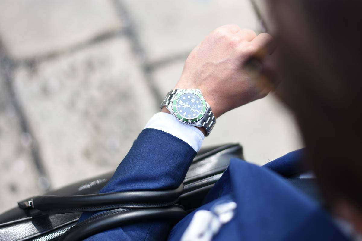 man in a suit checking his watch
