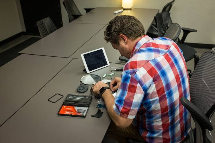 man sitting in a conference room trying to fix something with tools