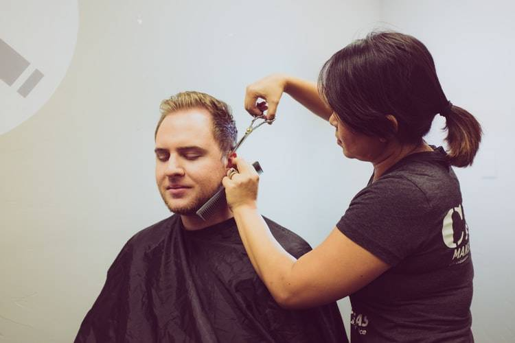 man closing his eyes getting haircut from a female hairdresser