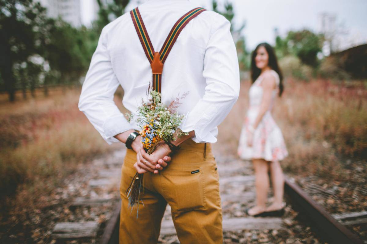man holding flowers behind his back with woman on train tracks