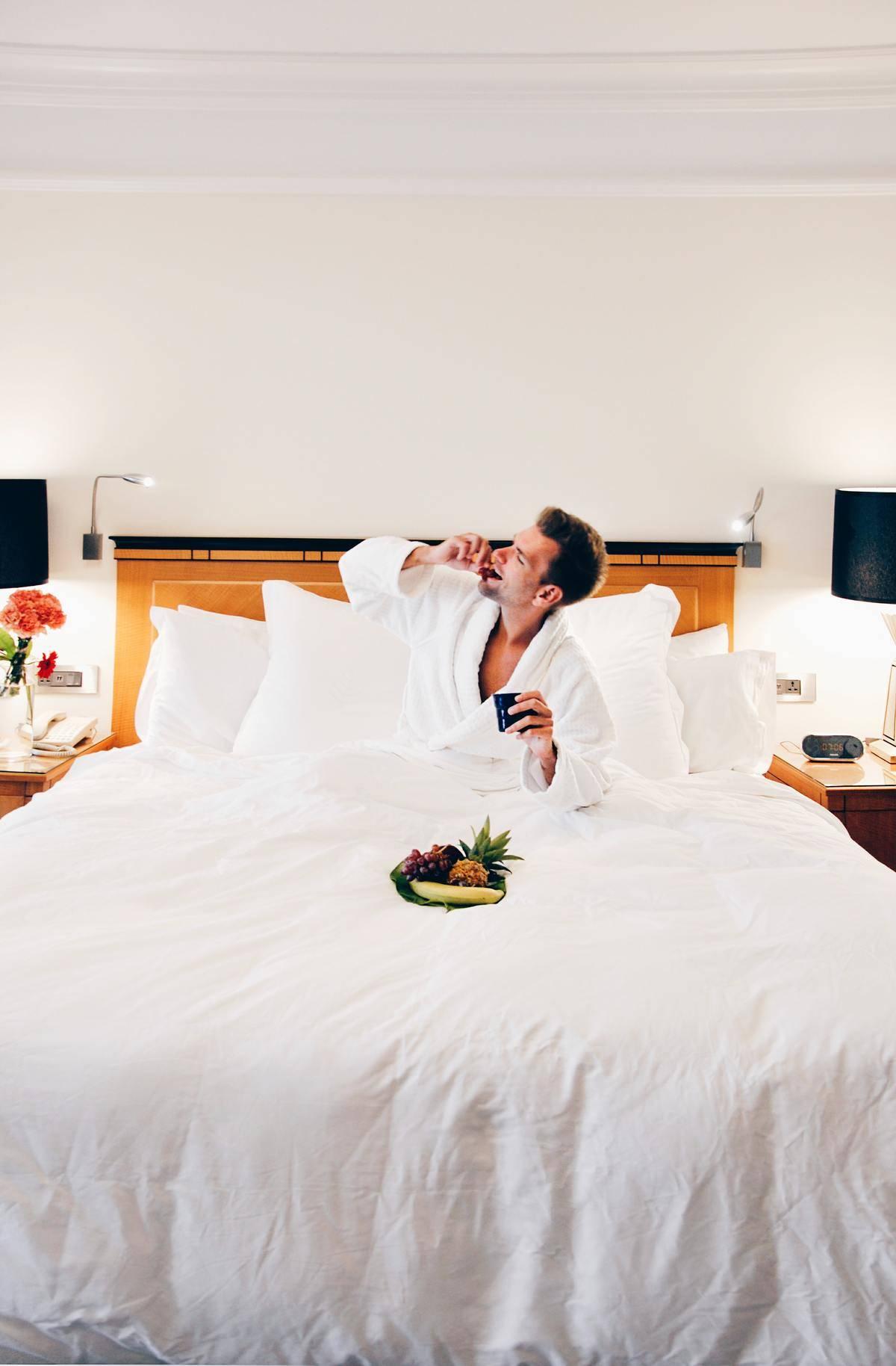man in hotel bed eating fruit