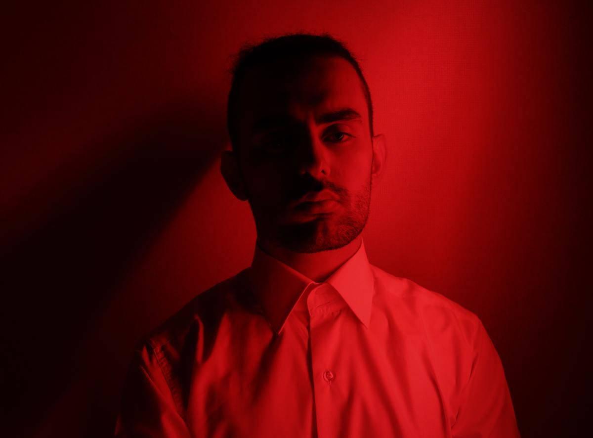 man in red lighting smirking