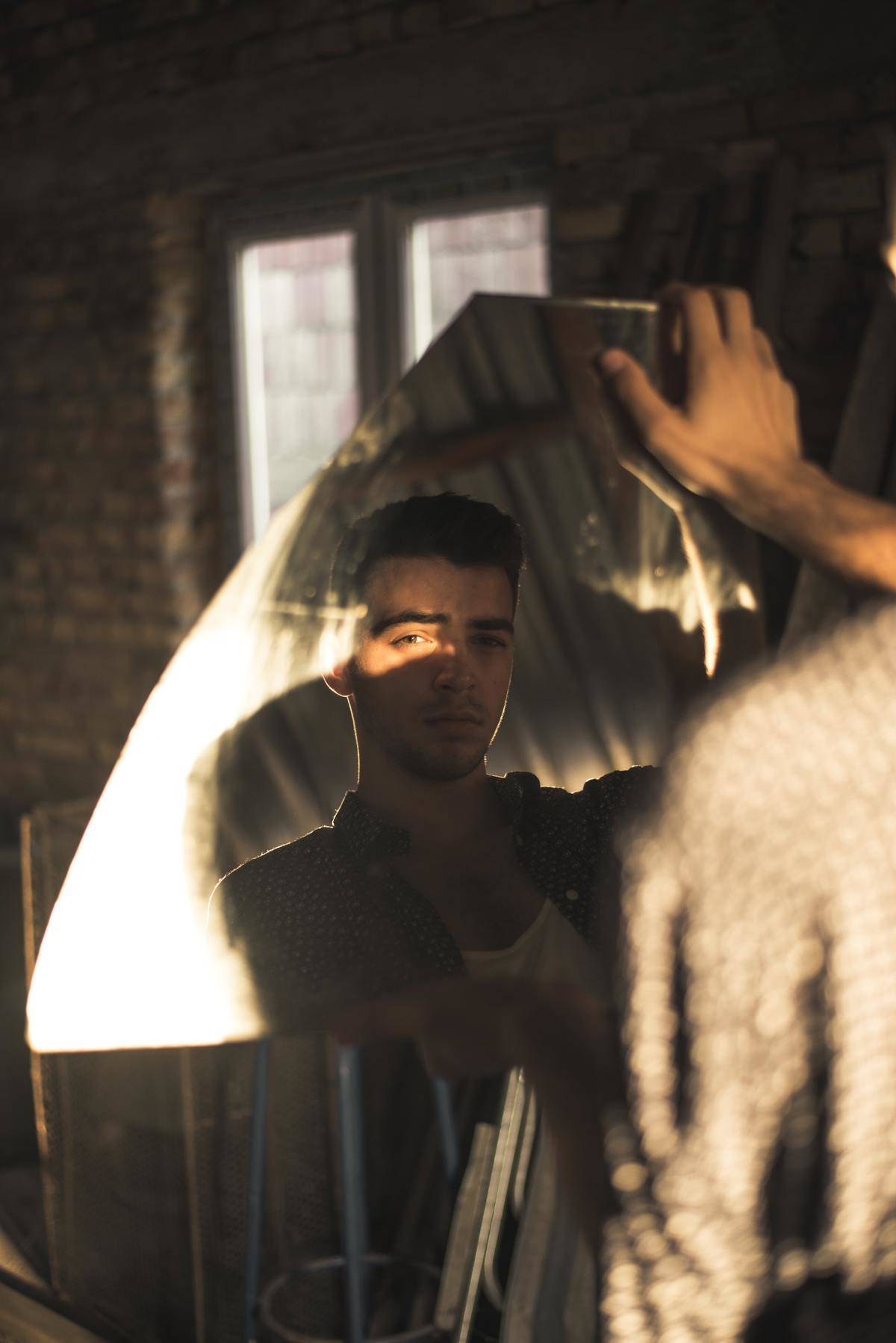 man looking into a broken mirror