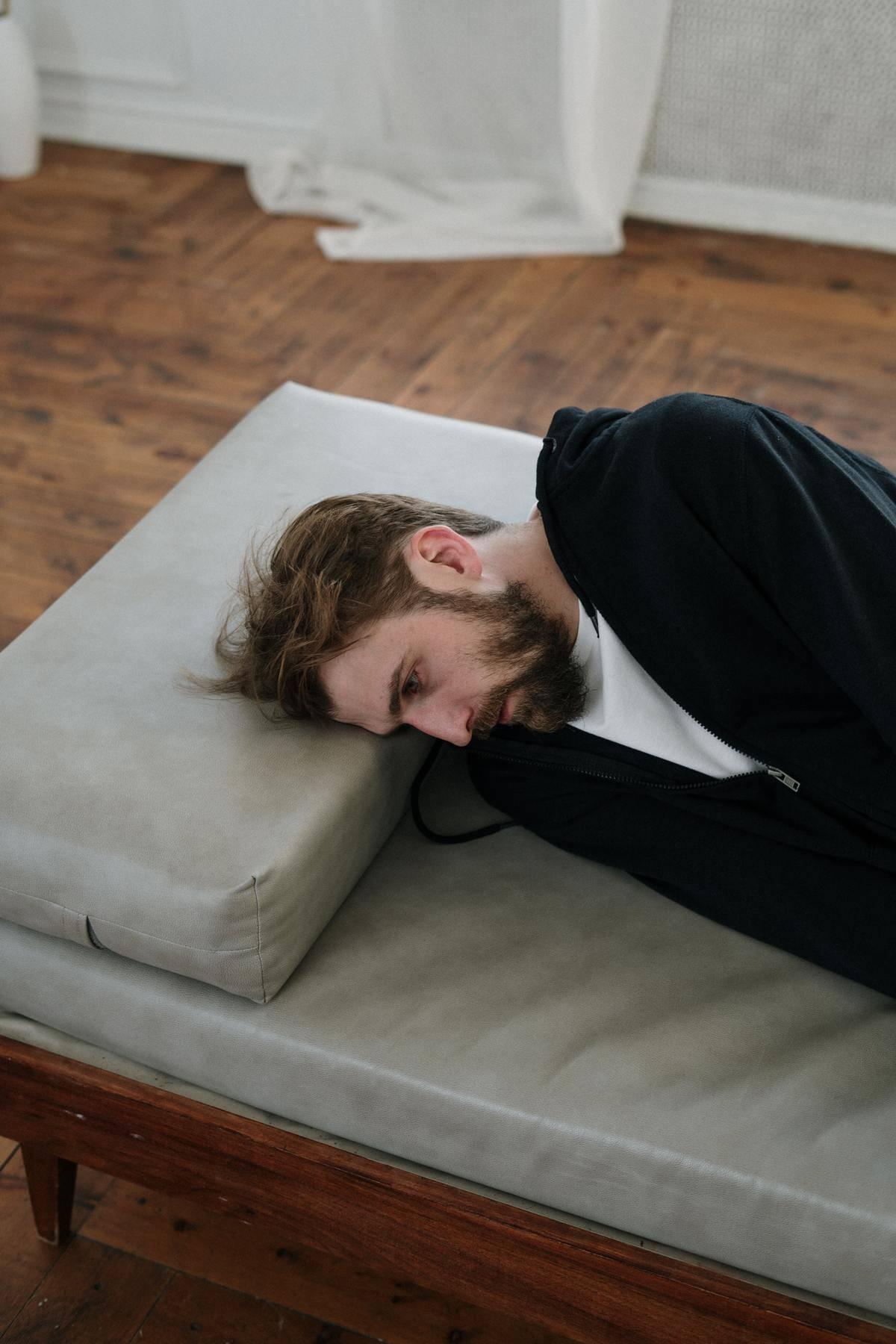 man lying down looking sad
