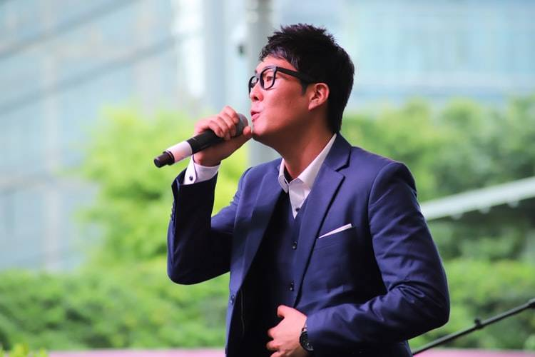 man dressed in a suit speaking into a microphone