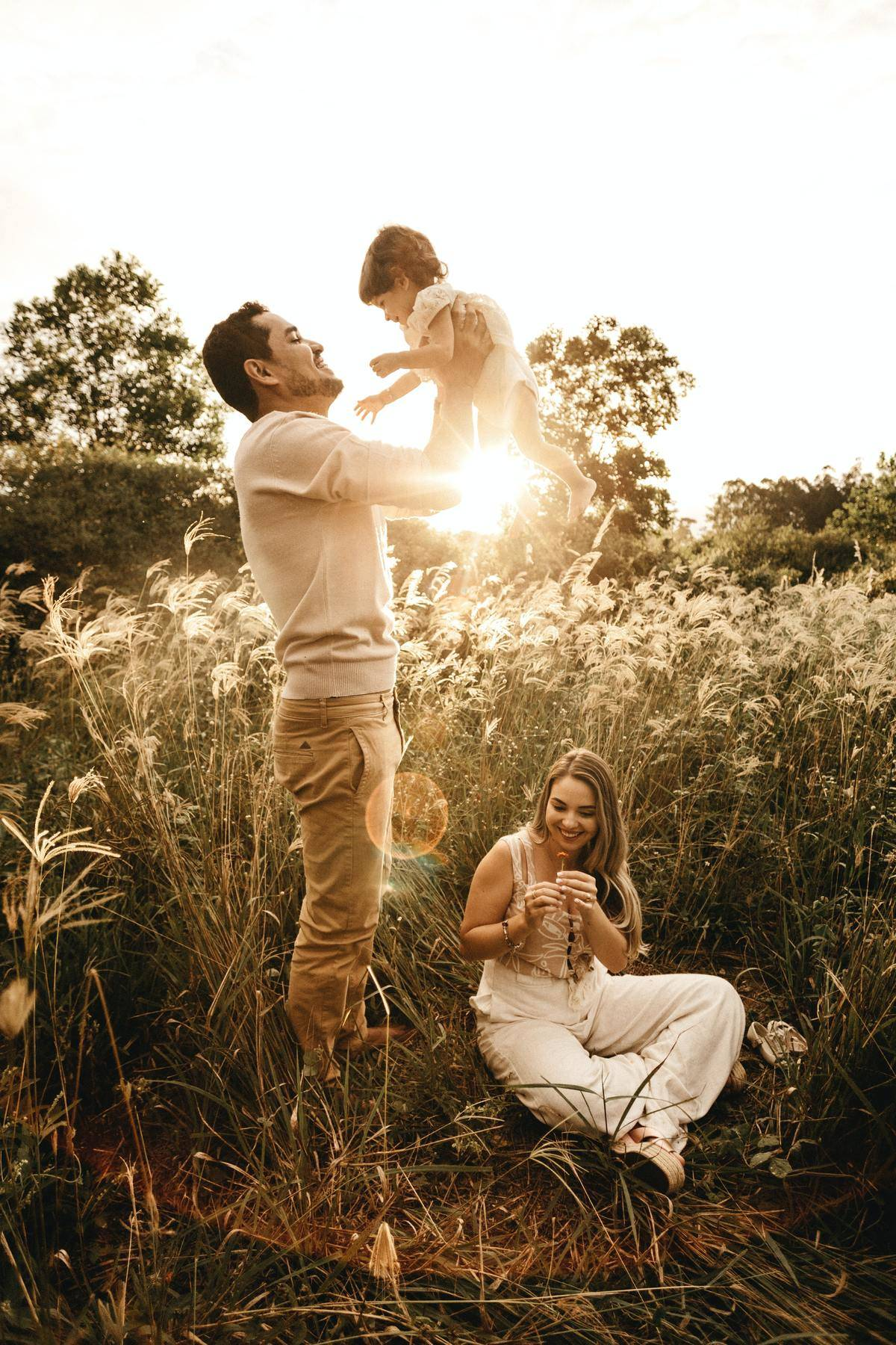man playing with baby in a field with woman sitting on ground