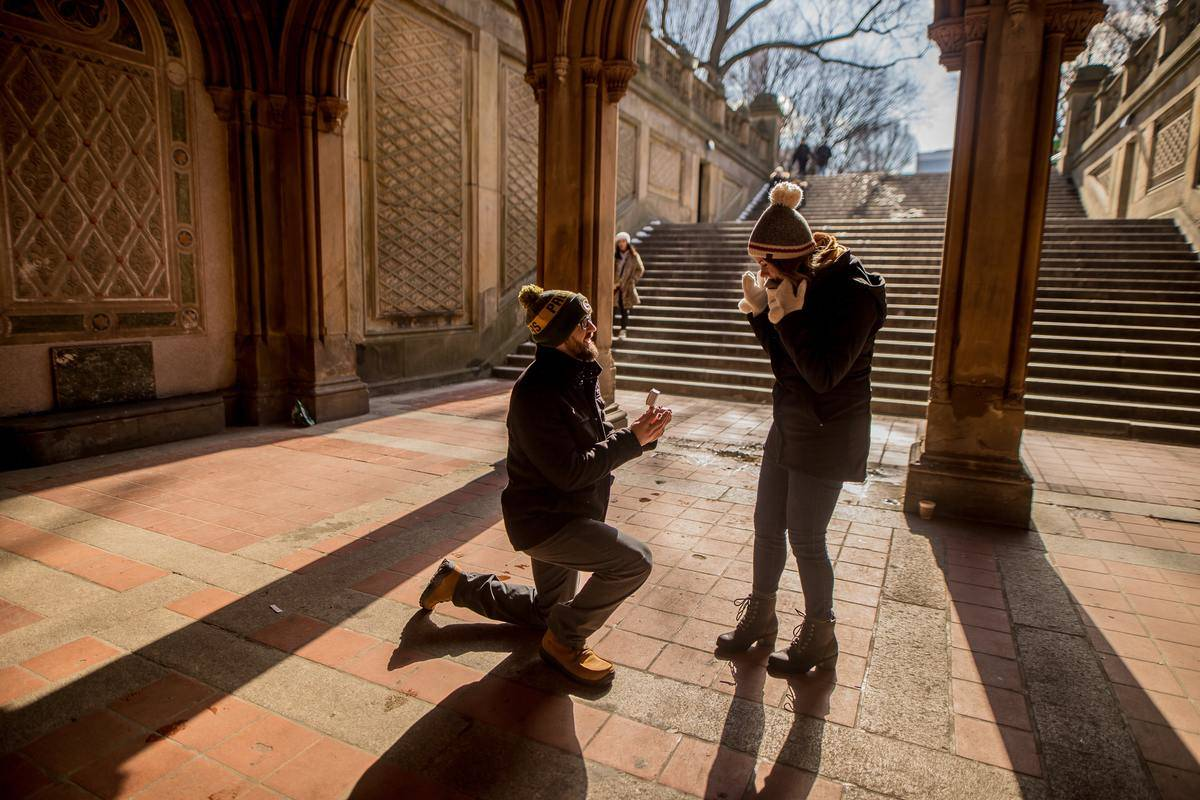 man proposes to woman in staircase