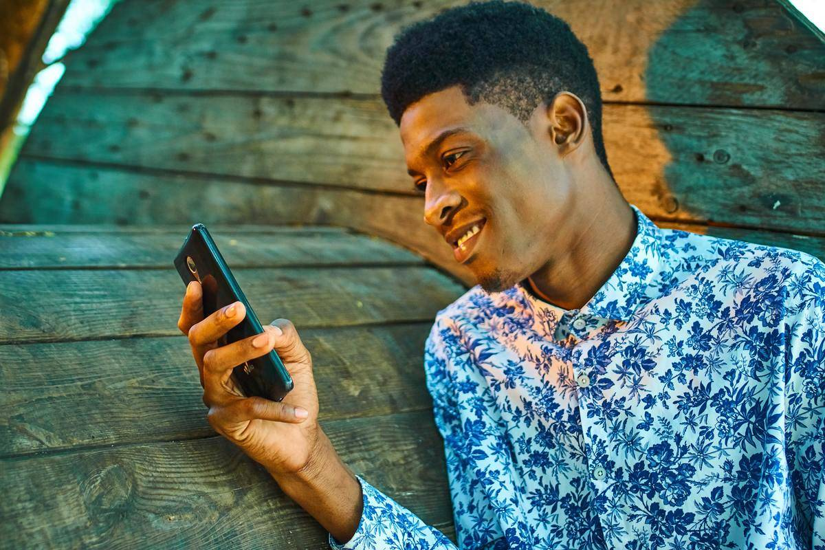 man reading his cellphone and smiling