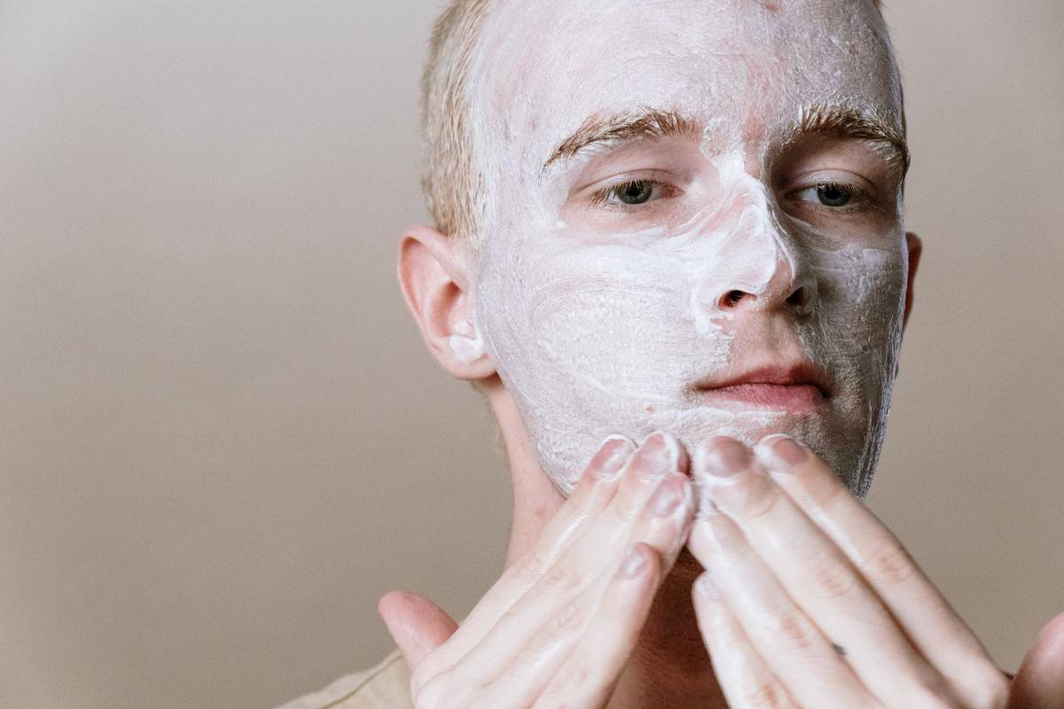 man washing his face with cream