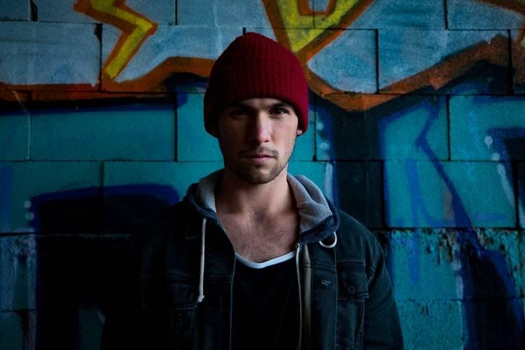 man in red beanie staring solemnly at camera against a graffiti wall background