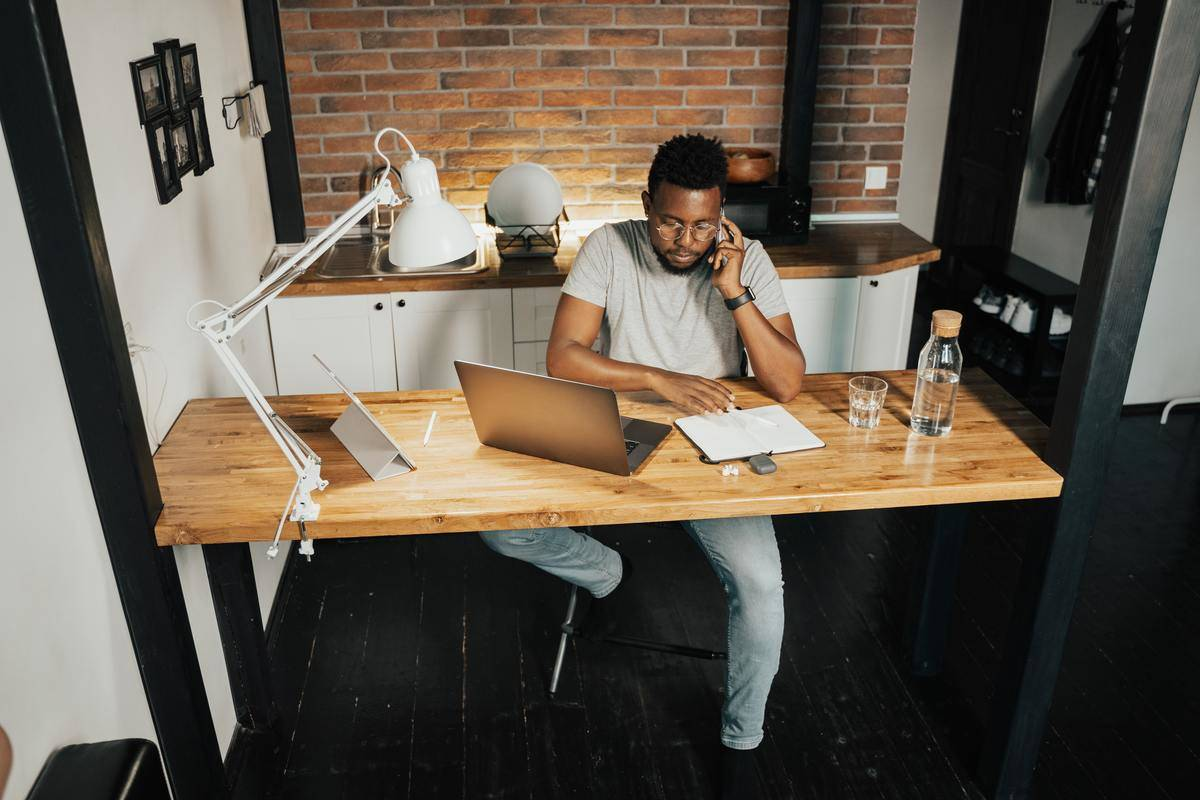 man working at desk on phone