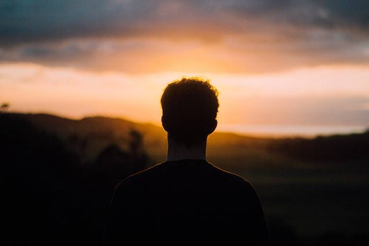 silhouette of man staring out at sunset