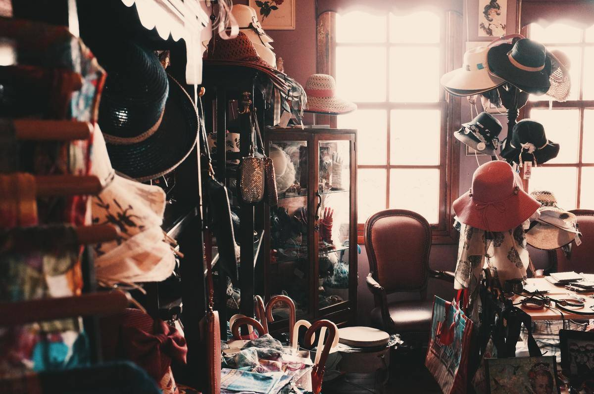 messy room with lots of hats hanging