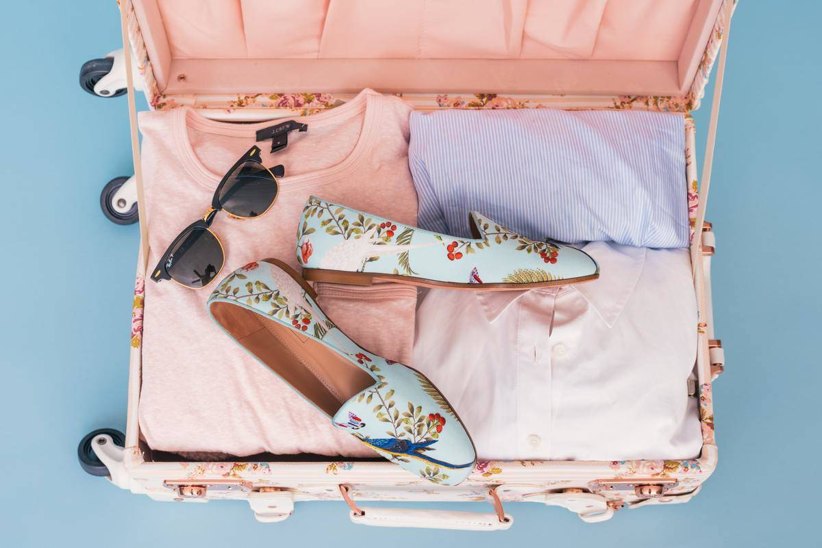 packed pink suitcase with shoes and sunglasses
