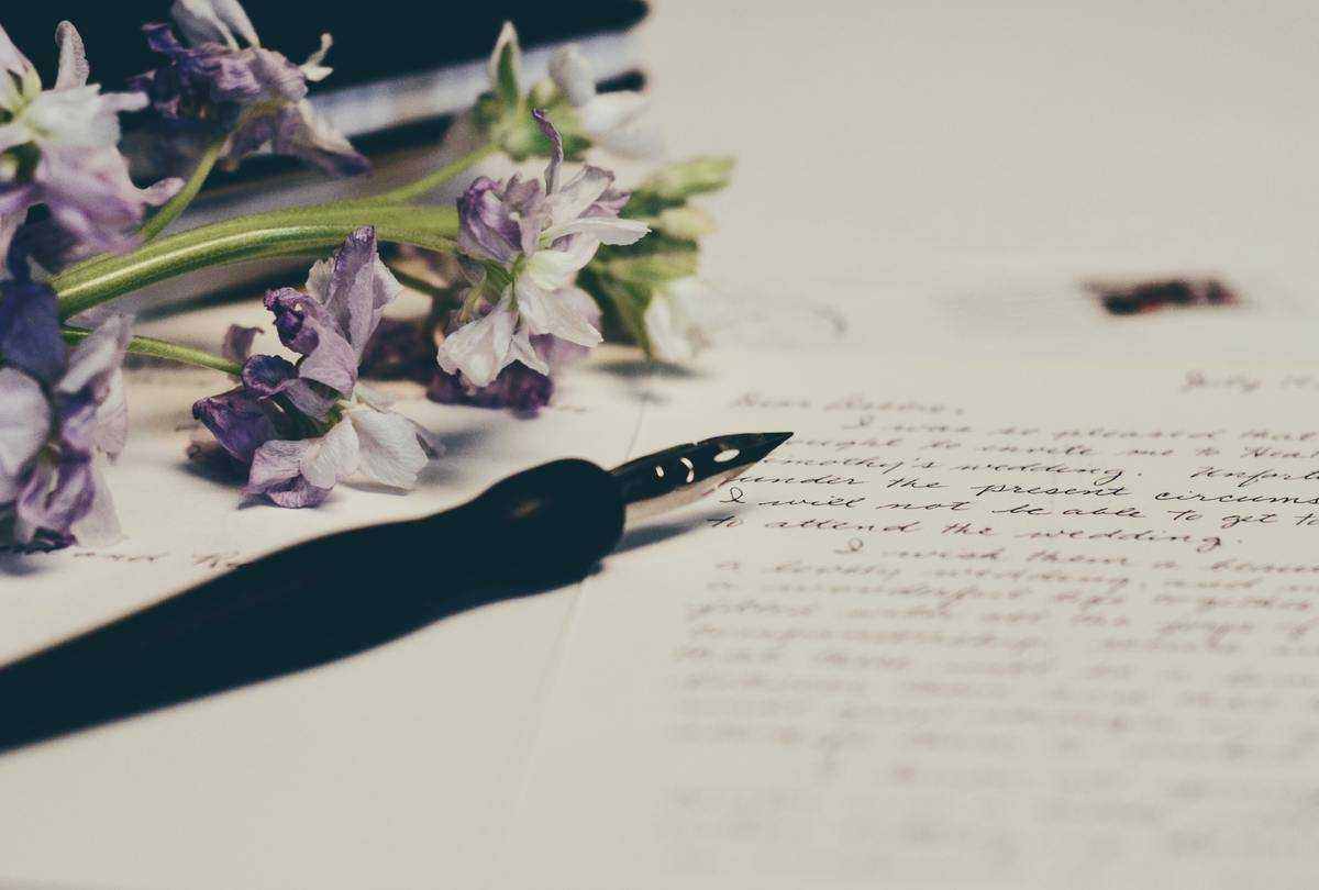 pen and paper for letter beside flowers