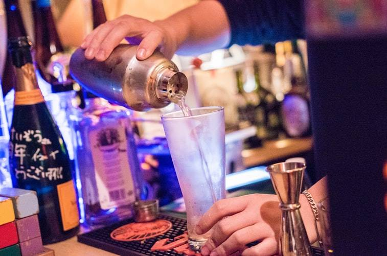 close up shot of a nightclub bartender pouring a drink through a shaker