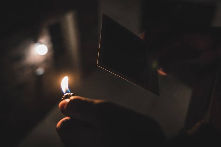 dark image of someone lighting a polaroid picture on fire