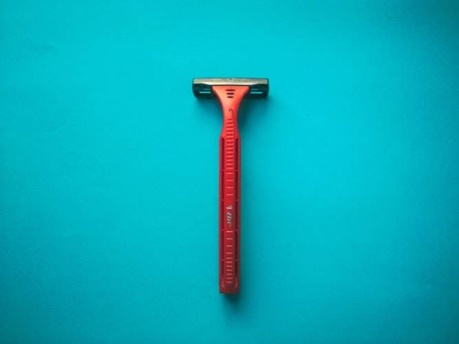 singular red razor against a bright turquoise background