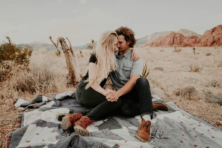 couple staring at each other and holding hands in the desert on a blanket