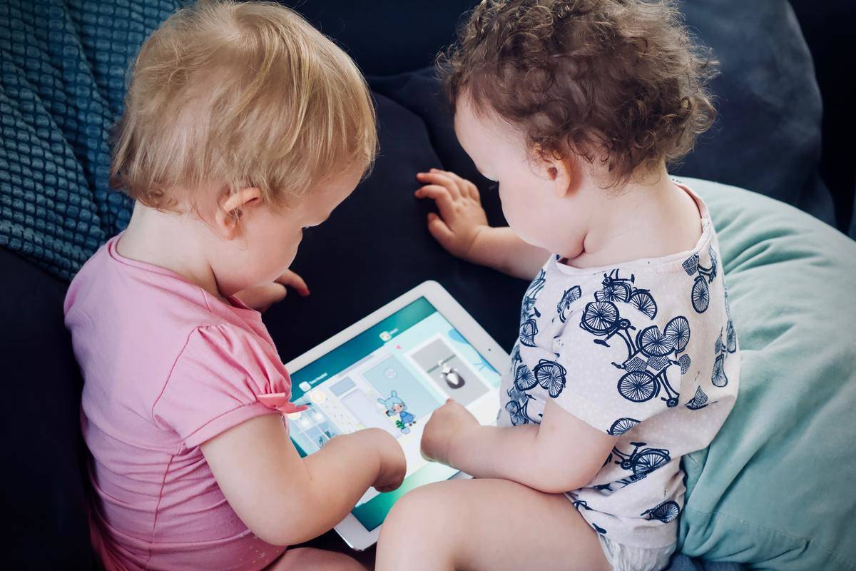 two babies playing with iPad on couch