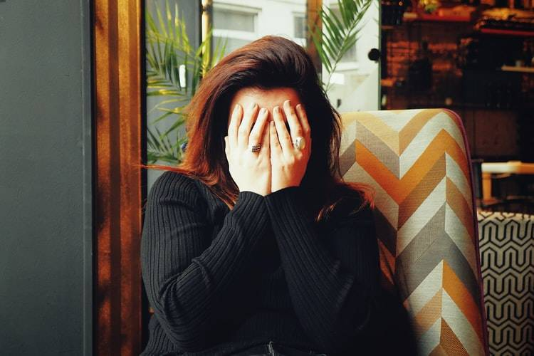 woman facing the camera with her hands over her face